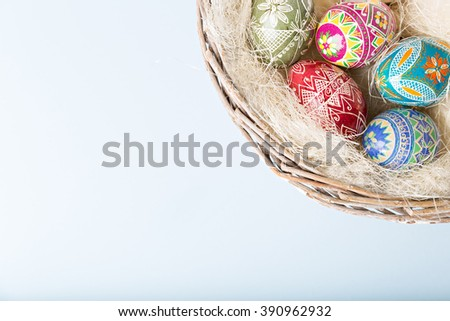 colorful shiny easter eggs in wicker basket - stock photo