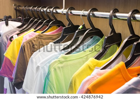 Colorful shirt in store. Dress hanger. Clothing hanger. Shirt hanger. Colorful shirt in shop. Cotton shirt. Hanging shirt. Hanging fashion shirt. Fashion shirt. Shirt background. Laundry hanging. - stock photo