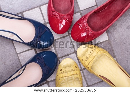 Colorful Shoes women's summer six pieces on a gray ceramic tile floor - stock photo