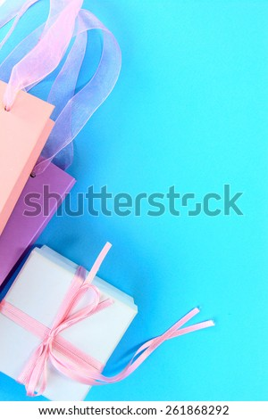 Colorful shopping bags and gift box on light blue background - stock photo