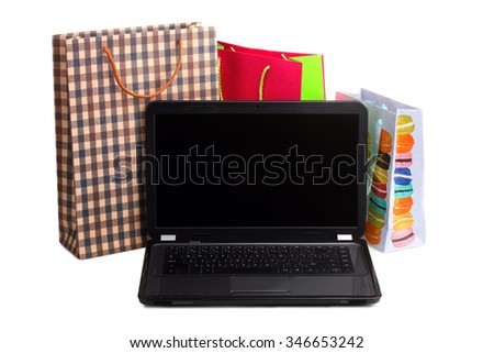 colorful shopping bags for shopping and an open laptop on a white isolated background - stock photo