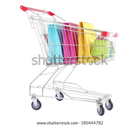 Colorful shopping bags in shopping trolley, isolated on white - stock photo