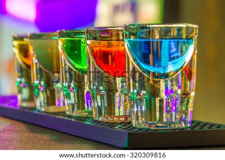 Colorful shot drinks in bar in night  - stock photo