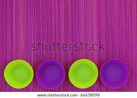 Colorful silicone baking cups on purple background - stock photo