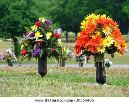colorful silk flower vases in summer cemetery - stock photo