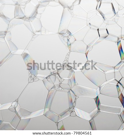 Colorful single plane of soap bubbles on a grey background