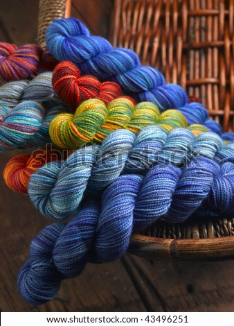 Colorful skeins of hand dyed yarn for knitting in brown wicker basket - stock photo