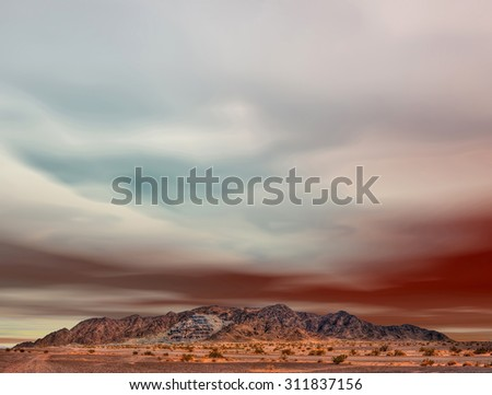 Colorful sky above Arizona desert mountain ravaged by mining - stock photo
