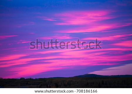 Colorful sky at sunrise over a hilly landscape