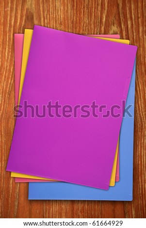 Colorful slim plastic binder isoleted on wood texture. - stock photo