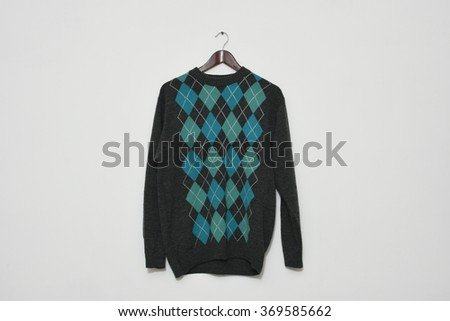 Colorful smart winter wear sweater on a hanger isolated on white wall background - stock photo
