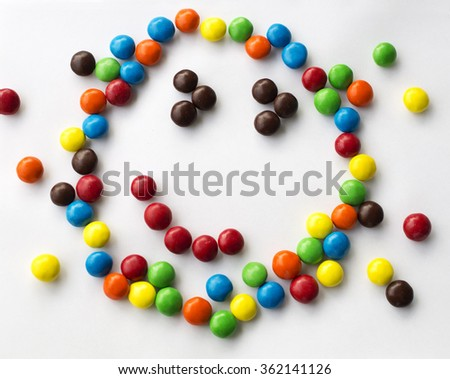 colorful smiley, kind, happy emotional candy face on white background made of round candies for children games  looks like cartoon face