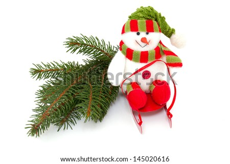 colorful snowman on sledges and twig of pine - stock photo