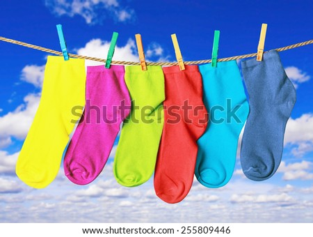 colorful socks hanging from a rope on the background of sky - stock photo
