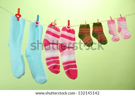 Colorful socks hanging on clothesline, on color background - stock photo