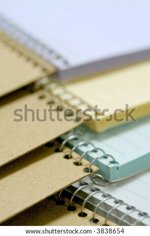 Colorful spiral bound notebooks stacked up in a row - stock photo