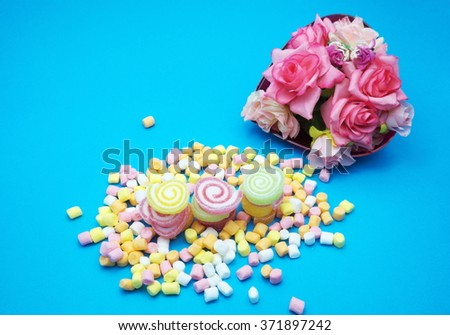 Colorful spiral jelly and colorful marshmallows on blue background, in red heart shaped box. Focus on jelly. - stock photo