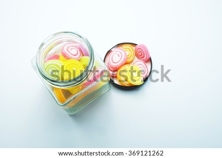 Colorful spiral jelly with glass jars on gray background. Focus on jelly on black lids. Space for texts. - stock photo