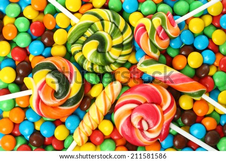 Colorful spiral lollipop with chocolate coated candy background  - stock photo