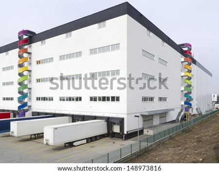 colorful spiral staircases against a large warehouse