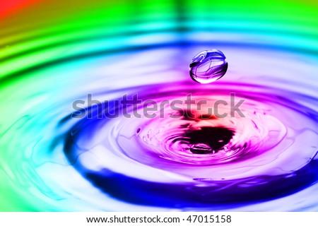 Colorful splash with round drop macro - stock photo