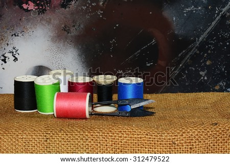 colorful spool of thread on old  sack background