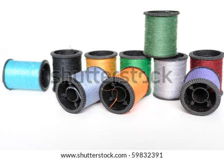 Colorful spools of thread in pile. - stock photo