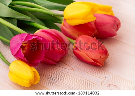 Colorful spring flowers bouquet tulips  on wooden background. Mother's Day holiday, birthday, beautiful background for card  - stock photo
