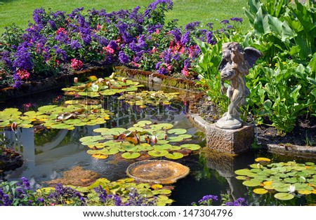 Colorful spring garden pond with cherub water fountain - stock photo