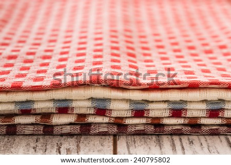 Colorful square checked kitchen napkins on white wooden table - stock photo