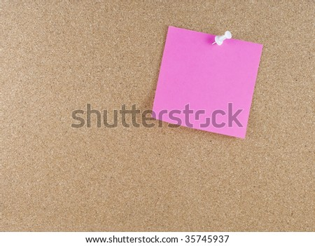 Colorful sticky blank note attached to a cork board white thumbtack