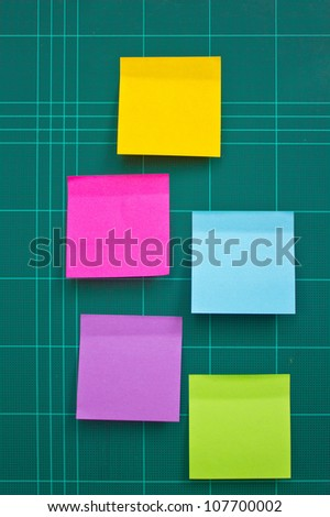 Colorful sticky notes on cutting mat. - stock photo