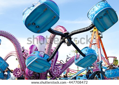 Colorful still life of a fun fair go around octopus hydraulics machine with swinging against the blue sky on a sunny day, outdoors. Dynamic movement recreational ride festival, exterior. - stock photo