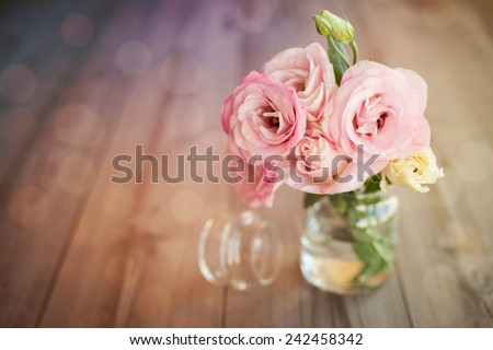 Colorful still life with roses in glass vase with bokeh background - stock photo