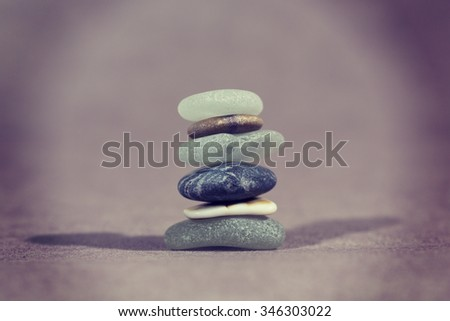 Colorful stones in a pile. This demonstrates nicely about the importance of teamwork. Every single individual is important for the whole team. Image has a vintage effect applied and has room for text. - stock photo