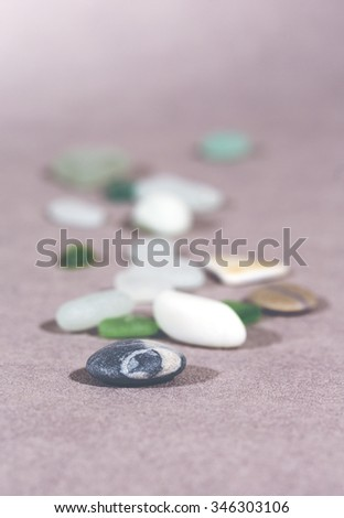 Colorful stones on the ground. This image shows tells that everyone is unique on it's different way but still important. Image has a vintage effect applied and has room for text embedding. - stock photo