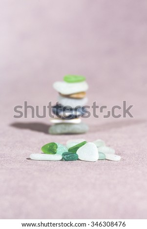 Colorful stones on the ground. This image shows that every individual is important for the whole team metaphorically speaking. A pile of stones in the background. Image has a vintage effect applied. - stock photo
