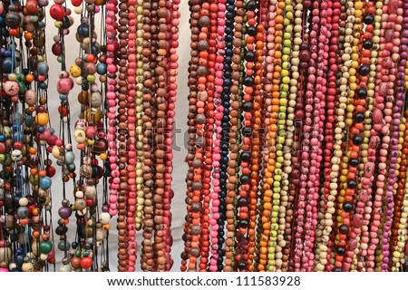 Colorful strands of handcrafted, carved Tagua beads hanging for sale at the outdoor craft market in Otavalo, Ecuador