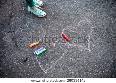 Colorful street chalk outdoors on asphalt with two hearts drawn to the ground