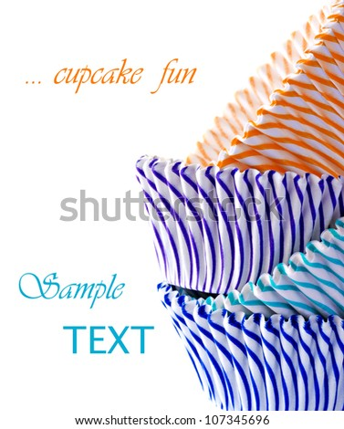 Colorful striped cupcake wrappers on white background with copy space. - stock photo