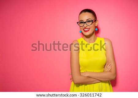 Colorful studio portrait of confident young brunette woman with hands crossed. Pink background. - stock photo