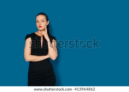 Colorful studio portrait of thoughtful young woman holding hand on chin. Doubt. Thinking about solution. Blue background isolated - stock photo