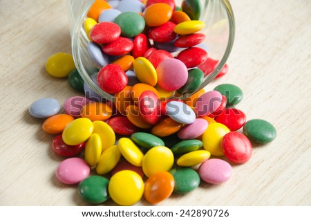 Colorful sugar-coated chocolate smarties in a glass - stock photo