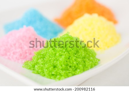 Colorful sugar on white plate with white paper background