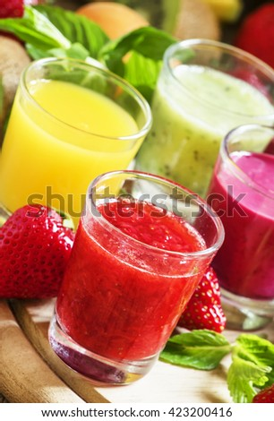 Colorful summer fruit and berry juices and smoothies in glasses: orange, strawberry, black currant, apple and kiwi, selective focus - stock photo