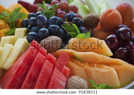 Colorful summer fruit platter with watermelon, cantaloupe, grapes, cherries, apricots, walnuts and mint - stock photo