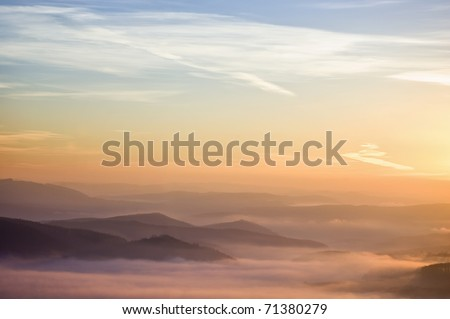 colorful summer morning with golden light and fog between hills - stock photo