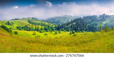 Colorful summer panorama of the foggy mountain village.