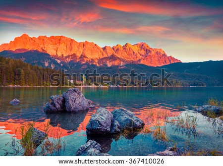 Colorful summer scene on the Eibsee lake in German Alps. Germany's highest mountain Zugspitze 2 962 m, and it's mountain ridge painted in red of the last rays of sunset. Germany, Europe. - stock photo