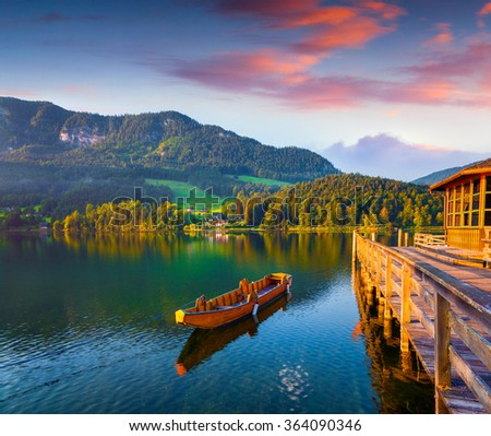 Colorful summer scene on the Grundlsee lake. Pier on Archkogl village with small pleasure launch. Alps, Austria, Europe. - stock photo